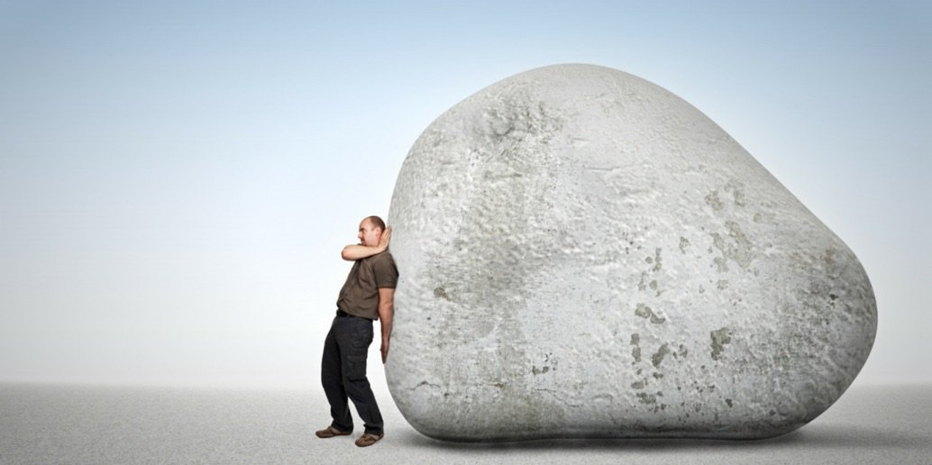 Image of a man trying to push a large and heavy boulder