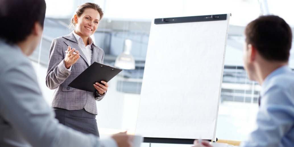 Image of a woman at a flip chart delivering leadership training