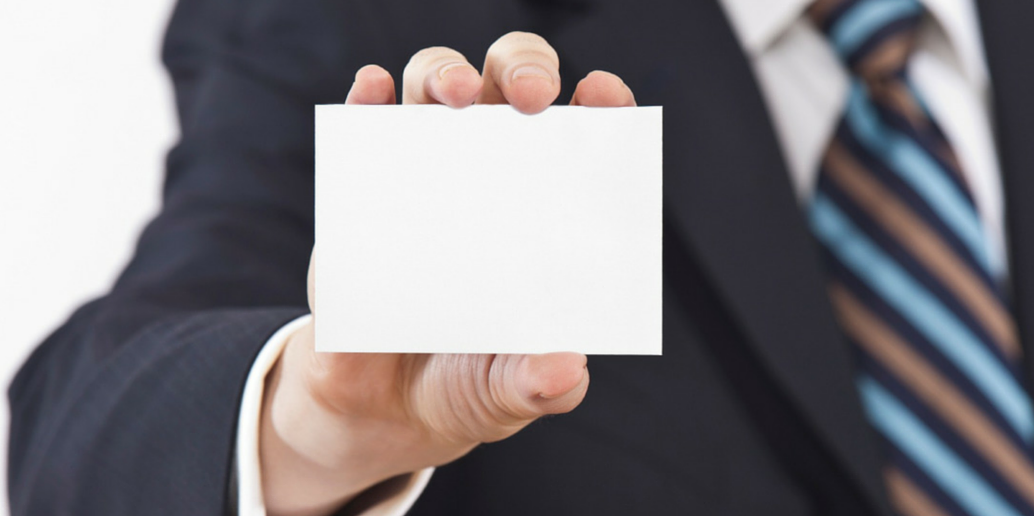 A hand holding up a blank business card