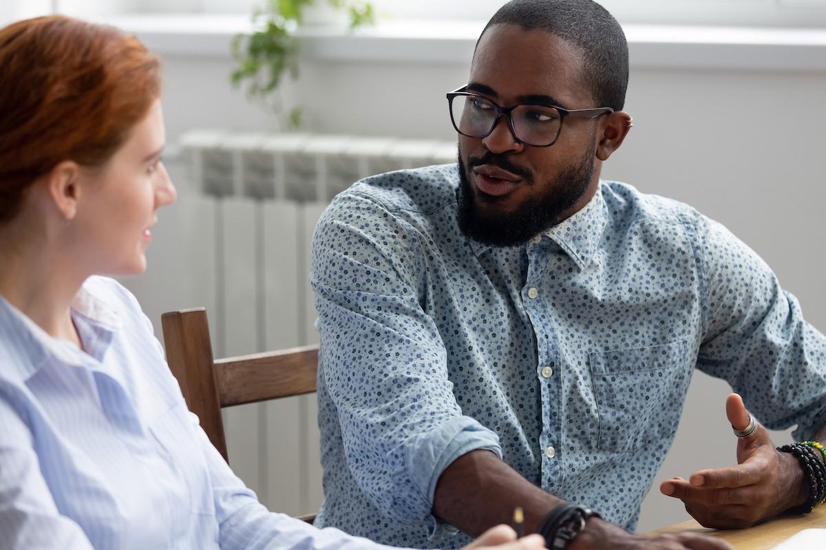 Organisations mentoring programme - black male mentor advising red haired female employee