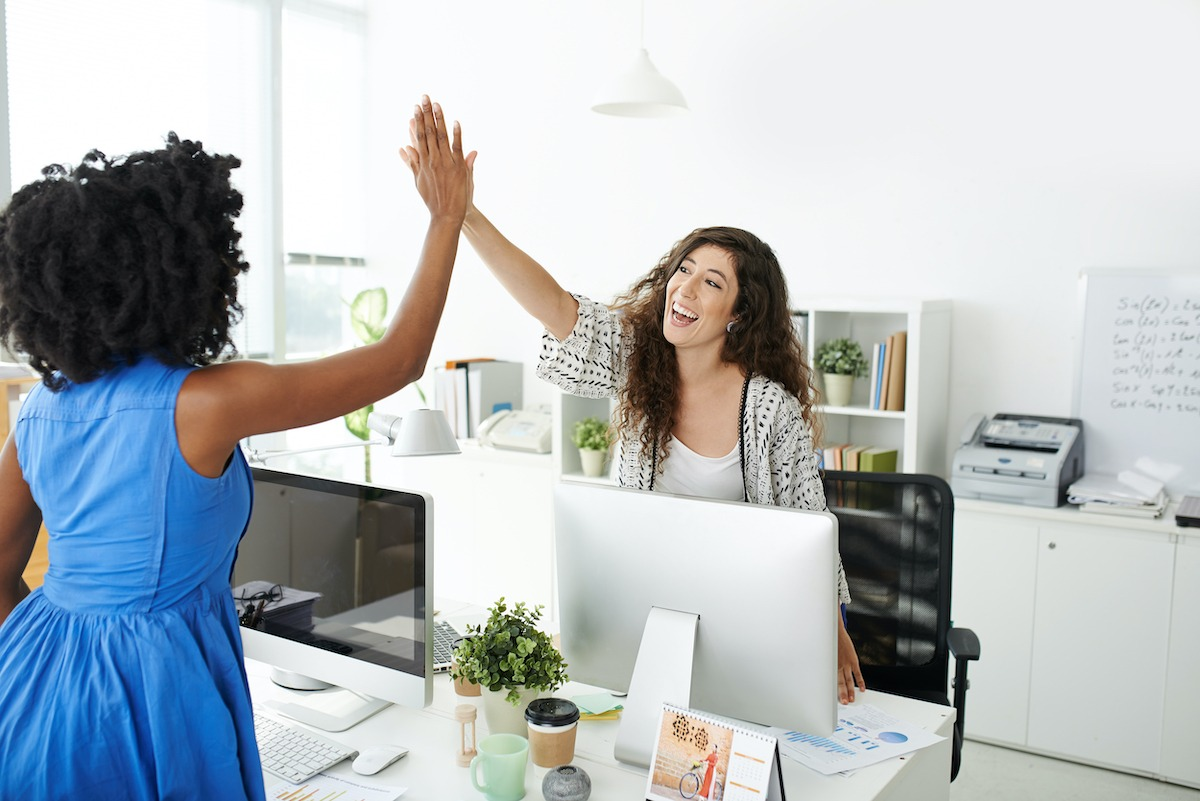 two women high fiving at work How to Get Mentors and Mentees Excited About Your Mentoring Programme