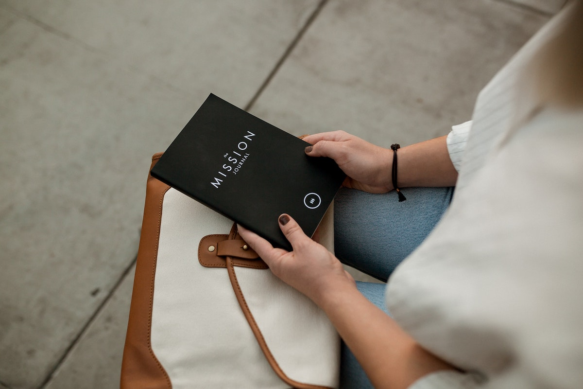 purpose at work person holding a journal with my mission written on the front